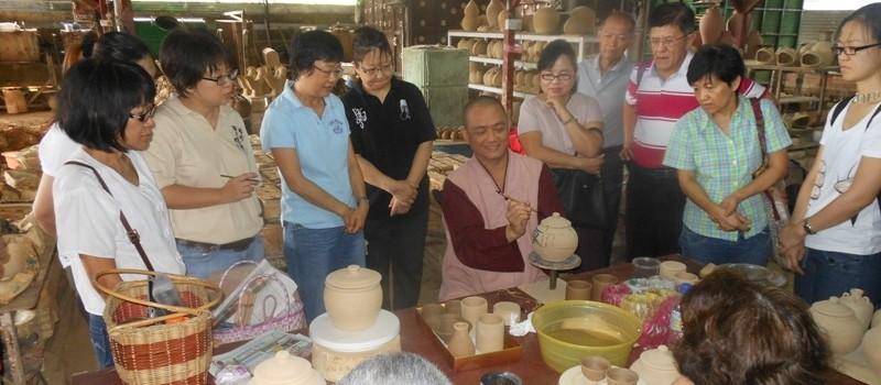 20130804 開印比丘(中)向學員示範在陶器上寫書法。